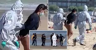 女性サーファーが防護服の警察官に手錠