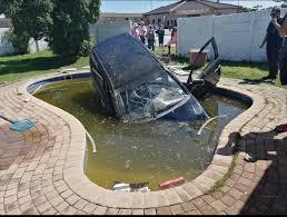 壁を破壊し民家のプールに突っ込む車