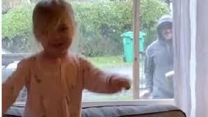 郵便配達員と窓越しにダンスする3歳の少女