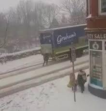 雪道で立ち往生する乳製品配達トラックを押して手伝った女性