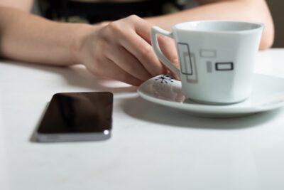 家庭でコーヒー片手にスマホ